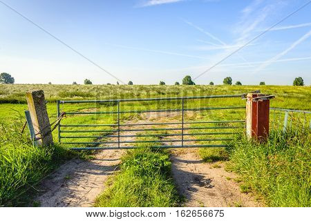 Clloseup of a galvanized steel gate between concrete poles in front of a Dutch embankment. The closed gate simply tied up with ropes.