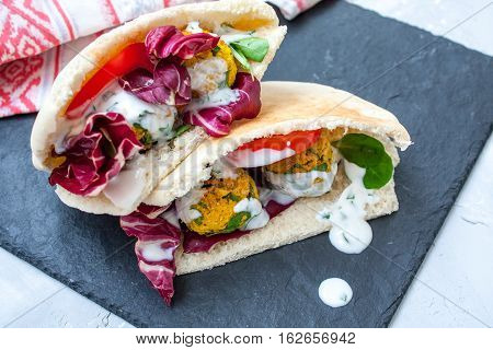 Falafel and vegetables in pita bread with a classic yogurt sauce. Concrete background.