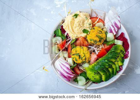 Vegan salad with falafel hummus vegetables. View top on gray concrete background. Vegan Food Concept.