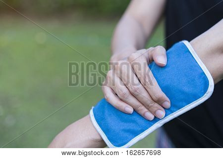 woman applying cold pack on her arm