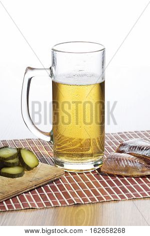 Glass of beer and salty fish on the wood table