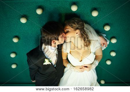 Couple Kisses On The Billiard Table Surrounded With White Balls