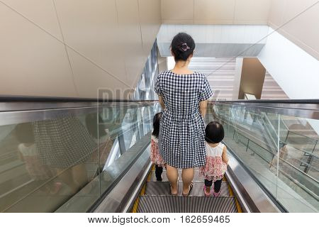 Asian Chinese mother and daughters taking escalator at MRT Station in Kuala Lumpur Malaysia. poster
