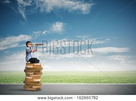 Kid of school age sitting on pile of books and looking in spyglass