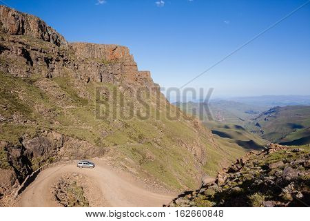 Mountains vehicle going down steep rugged mountain dirt road pass into valley landscape