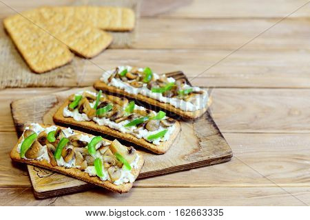 Diet snack with roasted mushrooms and fresh green bell pepper on a board and on a wooden background with copy space for text. Quick and healthy vegetarian snack. Homemade cuisine. Closeup