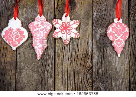 Gingerbread cookies hanging over wooden background. Copy spase.