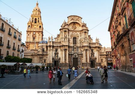 MURCIA SPAIN - JUNE 14 2014: Main facade of the Cathedral Church of Saint Mary in Murcia Spain. People at the square in front of the main landmark of the city