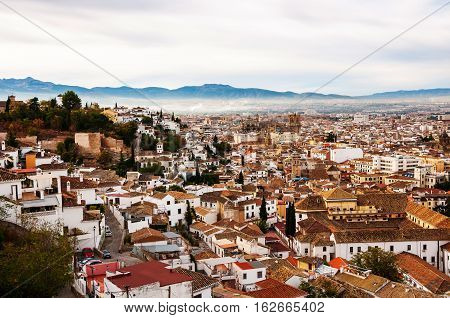Granada Spain. Aerial view of Granada - famous city in Andalusia Spain in the morning with mountains at the background. It is a UNESCO World Heritage Site and a major touristic attraction