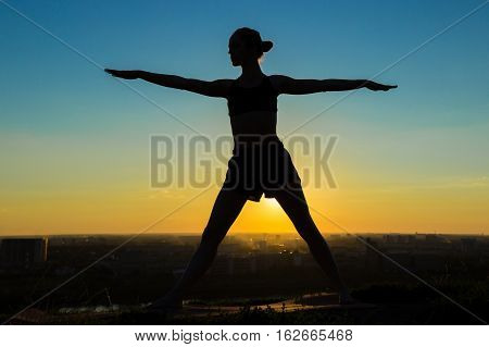Silhouette of sporty woman doing Ashtanga yoga in the park at sunset. Sunset light, sun lens flares, golden hour. Freedom, health and yoga concept