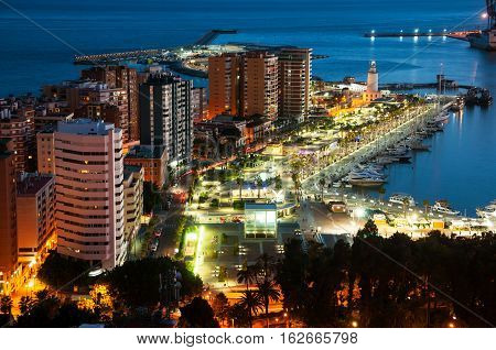 Malaga Spain. Aerial view of apartment buildings and hotels in Malaga Andalusia Spain with sea and port moored yachts at night