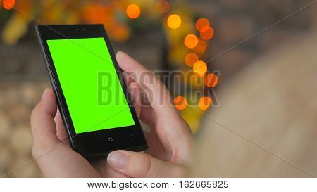 Woman looking at vertical smartphone with green screen. Close up shot of woman's hands with mobile. Elegant abstract garlands bokeh background