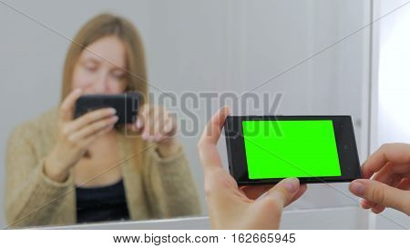 Woman sitting in front of a mirror and using horizontal smartphone with green screen. Close up shot of woman's hands with mobile Close up shot of woman's hands with mobile