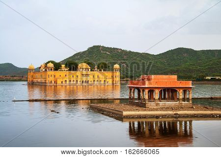 Jaipur India. Jal Mahal palace in the evening in Jaipur India. Popular landmark surrounded by water. Mountains at the background