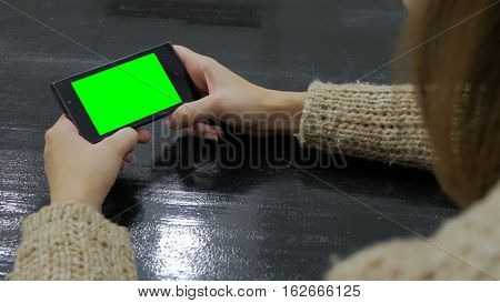 Woman looking at smartphone with green screen. Close up shot of woman's hands with mobile