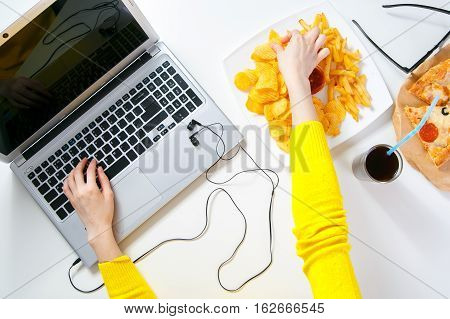 Pretty young woman working at the computer and eating fast food. Unhealthy Lifestyle
