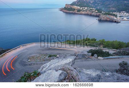 Mountain s-shape curved road near sea, harpin bend ultra wide angle, car light trail