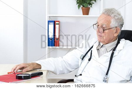 Old doctor with glasses thinking in consulting room