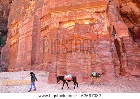 PETRA, JORDAN - MARCH 7, 2016: Colorful tombs in the Outer Siq with a local Bedouin leading his donkeys