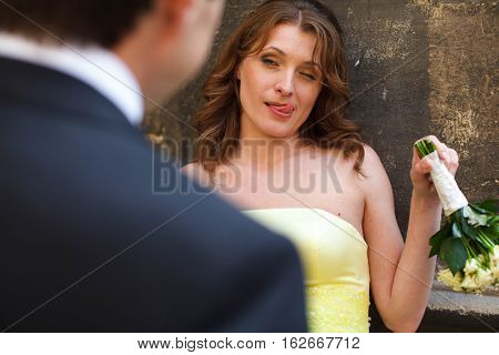 Bride in yellow dress looks sarcastic on the street