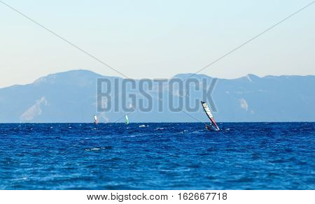 group of windsurfers on a background mountains in the Aegean sea