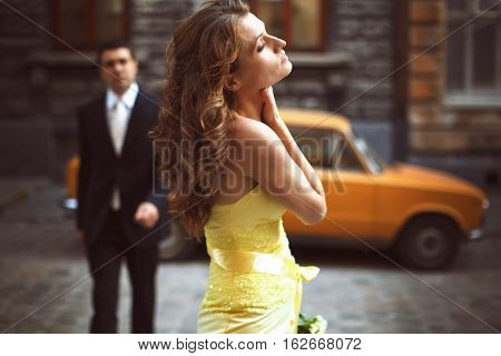 Lady In Yellow Stands Holding Her Nack And Eyes Closed