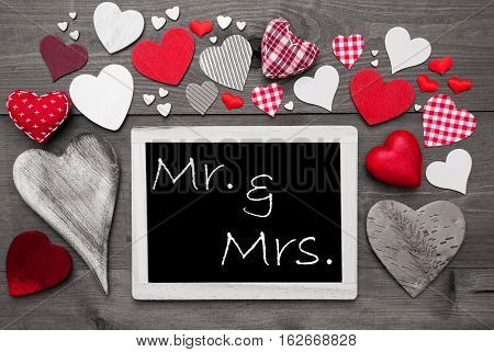 Chalkboard With English Text Mr And Mrs. Many Red Textile Hearts. Grey Wooden Background With Vintage, Rustic Or Retro Style. Black And White Style With Colored Hot Spots