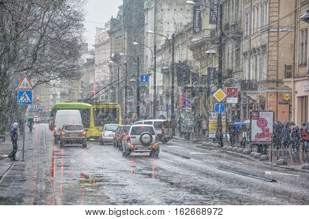 Lviv Ukraine - December 12 2016: Snowstorm with wet heavy snow and wind. Street view with cars and a lonely pedestrian