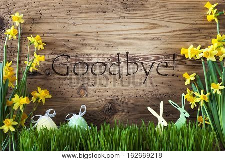 Wooden Background With English Text Goodbye. Easter Decoration Like Easter Eggs And Easter Bunny. Yellow Spring Flower Narcisssus With Gras. Card For Seasons Greetings