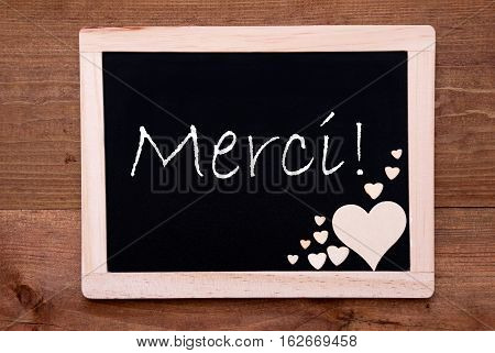 Blackboard With French Text Merci Means Thank You. Brown Wooden Hearts. Wooden Background With Vintage, Rustic Or Retro Style.