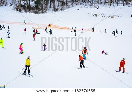 BUKOVEL, UKRAINE - December 17, 2016: Snowboarder and skiers enjoying on slopes of ski resort Bukovel. Bukovel is the most popular ski resort in Ukraine. Ski season and Winter sports concept