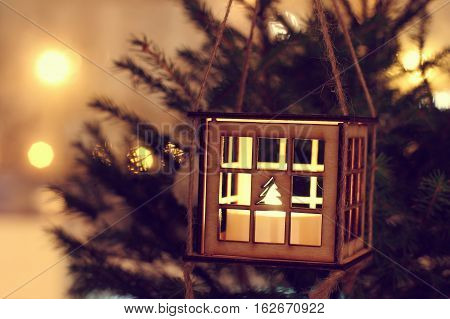 Wooden luminous lantern decorating this Christmas tree on the background New Year lights at night / cozy holiday atmosphere