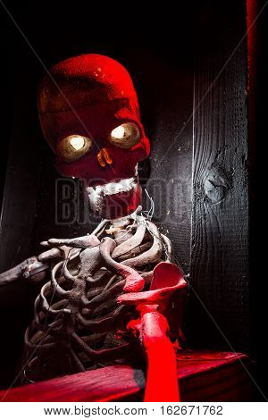 Red and white lit skeleton sitting and watching in a haunted house