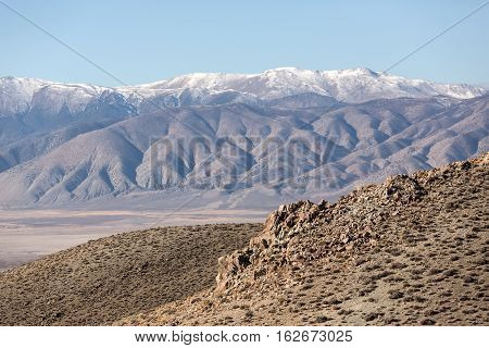 Craggy outcroppings desert plain and snowcapped mountain landscape