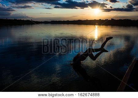 Reflection of the sun at sunset in the Limoncocha lagoon in the Ecuadorian Amazon