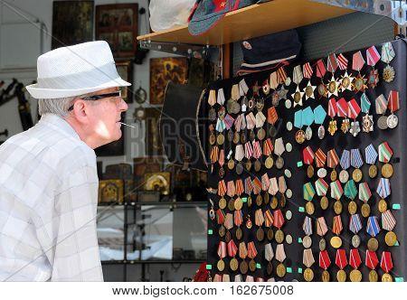 NESEBAR BULGARIA - SEPTEMBER 8 2016: Elderly man looks at military awards on display in the souvenir shop