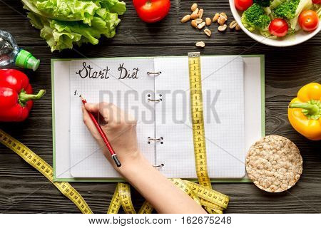 concept diet and slimming plan with vegetables top view mock up on wooden background
