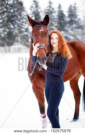 Young teenage girl standing with bay horse in winter park