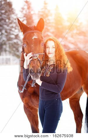Young teenage girl standing with bay horse in winter park at sundown