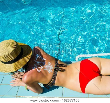 Photo of the Woman relax near swimming pool in hat and red panties. 2017 written on back by suncream. Celebrating new year in tropical country concept.