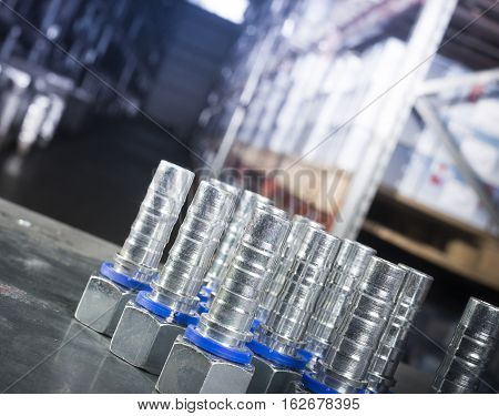 Metal hydraulic fittings stands on the silver table in the warehouse