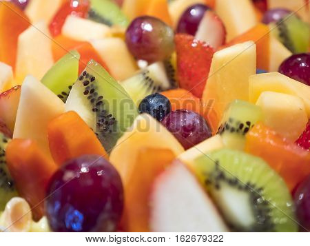 Closeup of sweet dessert mix fruit cake (kiwi cantaloupe blueberry blackberry strawberry grape papaya) selective focus