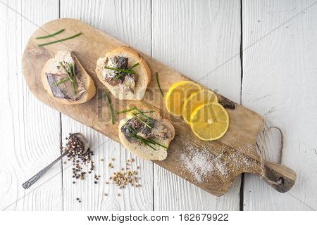 Sandwiches with sardines on a cutting board