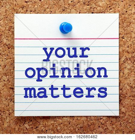 The words Your Opinion Matters in blue text on a note card pinned to a cork notice board as a reminder of the importance of customer feedback