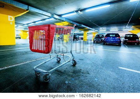 Abandoned empty cart in shopping mall underground garage parking lot retail and consumerism concept