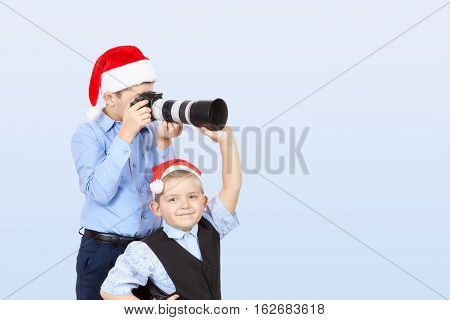 Brother helps brother to photograph in a cap of Santa Claus