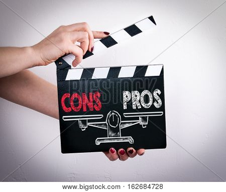 Pros and Cons Balance. Female hands holding movie clapper.