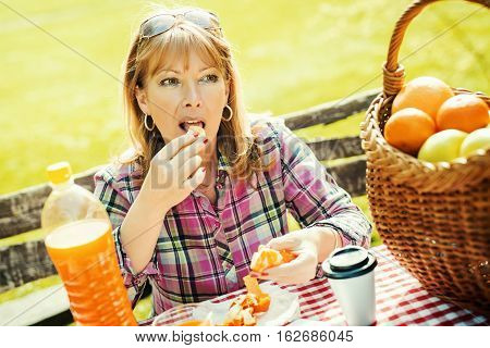 Portrait of a smiling mid adult lady enjoying in fruit on a picnic