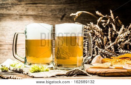 Beer mug with hop and wheat and potato chips on cloth on wooden table