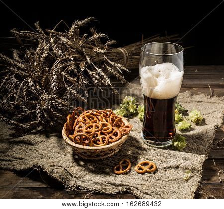 Glasse beer with wheat and hops, basket of pretzels on linen cloth on wooden table